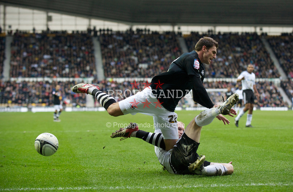 DERBY, ENGLAND - Saturday, March 12, 2011: Swansea City's Angel Rangel is tackled by Derby County's Gareth Roberts during the Football League Championship match at Pride Park. (Photo by David Rawcliffe/Propaganda)