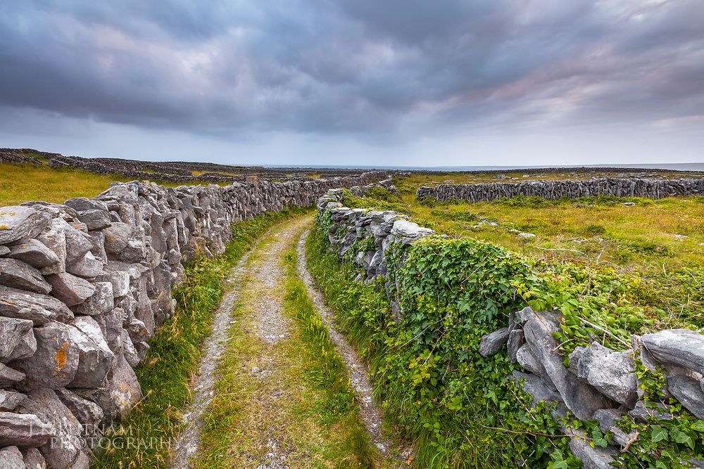 A carriage road runs between stone walls in a picturesque scene on Inisheer, one of the Aran Islands of Ireland.