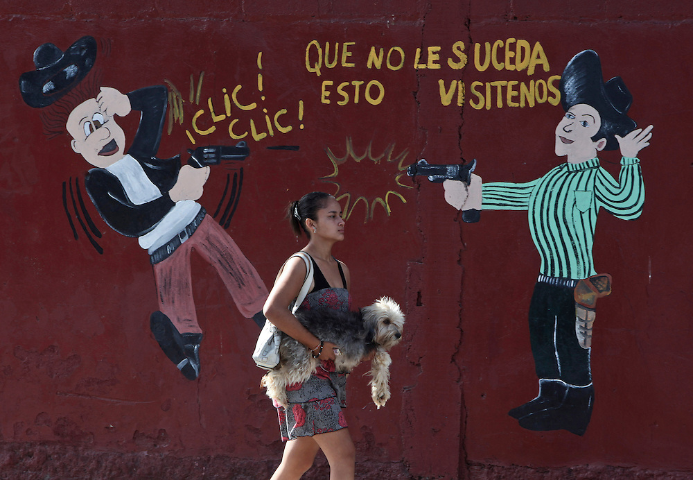 In this March 11, 2012 photo, a woman carries her dog past an armory shop in San Pedro Sula, Honduras. A wave of violence has made Honduras among the most dangerous places on Earth, with a homicide rate roughly 20 times that of the U.S. rate, according to a 2011 United Nations report.