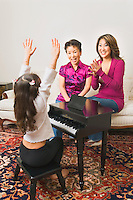 Mother and grandmother applauding young girl performing on toy piano.