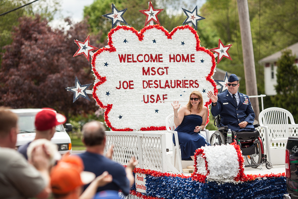 Injured Air Force Master Sgt. Joseph Deslauriers Jr. rides on a float with his wife Lisa in a Memorial Day parade where he served as grand marshall in his home town of Bellingham, MA on Sunday, May 19, 2013. The parade was held a week before the holiday to ensure greater attendance. In 2011, Deslauriers lost both of his legs and part of an arm after stepping on an explosive device while stationed in Afghanistan. He is currently rehabbing at Walter Reed Army Medical Center.  (Matthew Cavanaugh for The Washington Post)