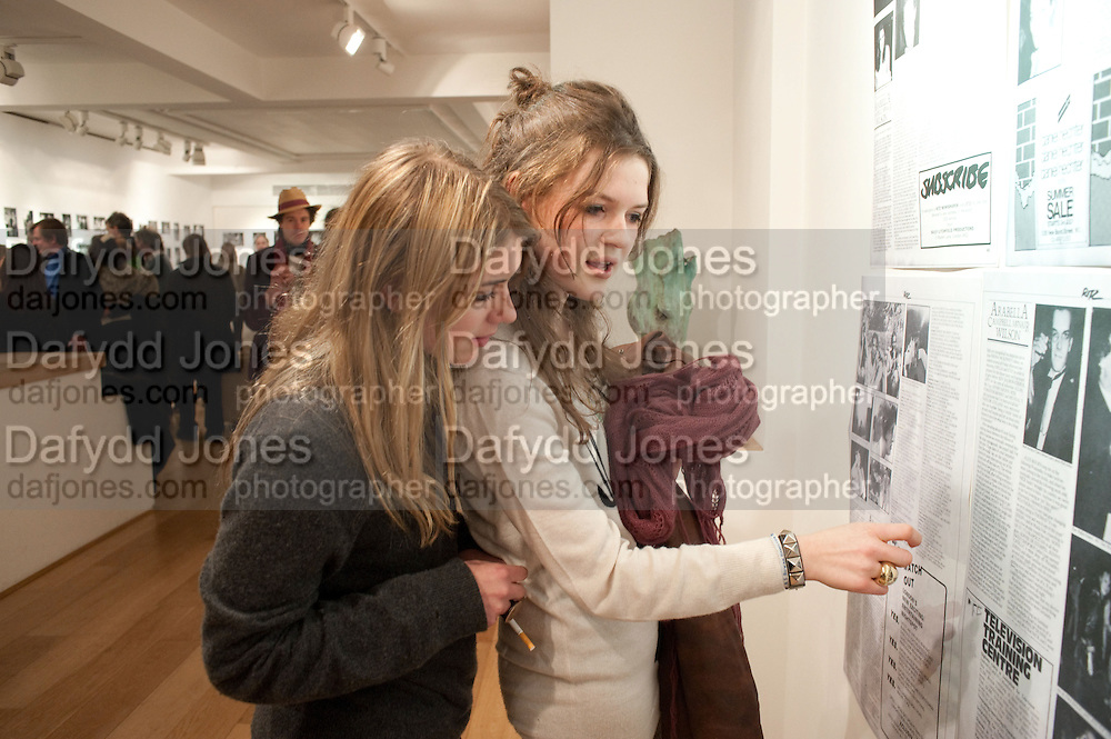 MOLLY ROWAN-HAMILTON; CLAUDIA GUINNESS LOOKING AT OLD PAGES FROM RITZ MAGAZINE WITH PHOTOS BY NICK ASHLEY AND COLUMN BY ARI. The Way We Wore.- Photographs of parties in the 70's by Nick Ashley. Sladmore Contemporary. Bruton Place. London. 13 January 2010.