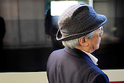 elderly man standing and waiting for train