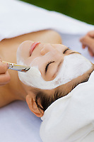 Young woman having facial treatment, close-up