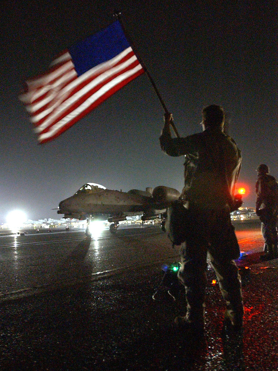 """OLD GLORY.First Sgt. Kent Fuller from the 332nd Expeditionary Maintenance Squadron at an undisclosed air base in the middle east, waves his """"retirement Flag"""" at departing aircraft headed for Iraq. He is from the 31st Fighter Squadron in Aviano, Italy. He got his deployment orders and his retirment orders on the same day so he got this flag to cheer on the pilots during his final deployment."""