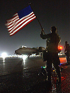 "OLD GLORY.First Sgt. Kent Fuller from the 332nd Expeditionary Maintenance Squadron at an undisclosed air base in the middle east, waves his ""retirement Flag"" at departing aircraft headed for Iraq. He is from the 31st Fighter Squadron in Aviano, Italy. He got his deployment orders and his retirment orders on the same day so he got this flag to cheer on the pilots during his final deployment."
