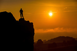 © Licensed to London News Pictures. 13/09/2016. Ilkley UK. A man stands on top of the Cow & Calf rocks at Ilkley Moor 1,319ft above the fog covered town of Ilkley to watch this morning's sunrise on what is predicted to be the hottest day in September. Photo credit: Andrew McCaren/LNP