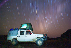 Star trails encircle a tourist vehicle in the southern hemisphere of Namibia's Skeleton Coast, Skeleton Coast, Namibia,Africa