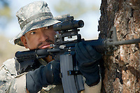 Soldier aiming machine gun, close-up