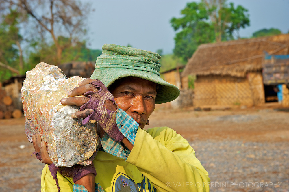 A man carries a rock at a breaking stones site.