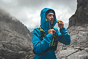 Portrait of a trail runner wearing a hooded jacket on a rainy day close to Collado Jermoso, Leon, Spain Trail runner running uphill in Collado Jermoso, Picos de Europa National Park, Spain