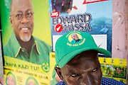 Dar es Salaam, Tanzania - 22.10.15  -  A Chama Cha Mapinduzi (CCM) supporter sits next to a wall covered in election posters in downtown Dar es Salaam, Tanzania on October 22, 2015.  Photo by Daniel Hayduk