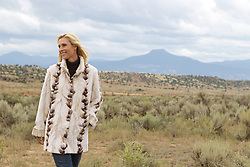 woman in a fur coat walking in Abiquiu, NM