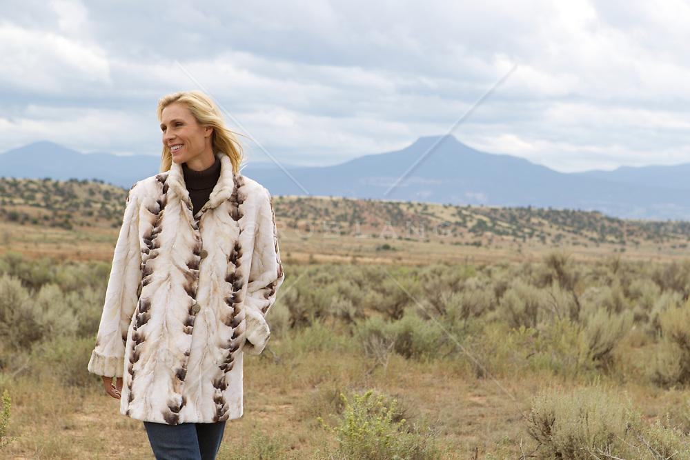 woman in a fur coat walking in Abiquiu, NM