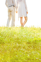 Midsection of couple holding hands while standing on grass against sky