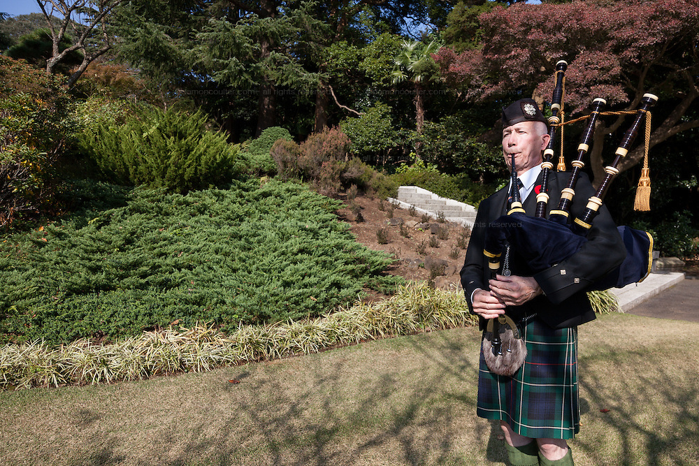 Bagpiper,, Frank Hunter plays during the ceremony for Remembrance Sunday at the Commonwealth War Graves Cemetery in Hodogaya, Yokohama, Japan. Sunday November 13th 2016. Each year representatives of the Commonwealth nations, along with American and other European nations that lost servicemen fighting the Japanese in World War 2, hold a multi-faith service of remembrance at this cemetery. This is the only cemetery for war dead in japan that is managed by the Commonwealth War Graves Commission.