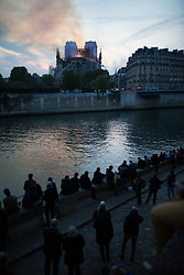 Bystanders look on as flames and smoke are seen billowing from the roof at Notre-Dame Cathedral in Paris on April 15, 2019. A fire broke out at the landmark Notre-Dame Cathedral in central Paris, potentially involving renovation works being carried out at the site, the fire service said.Images posted on social media showed flames and huge clouds of smoke billowing above the roof of the gothic cathedral, the most visited historic monument in Europe. Photo by Raphael Lafargue/ABACAPRESS.COM