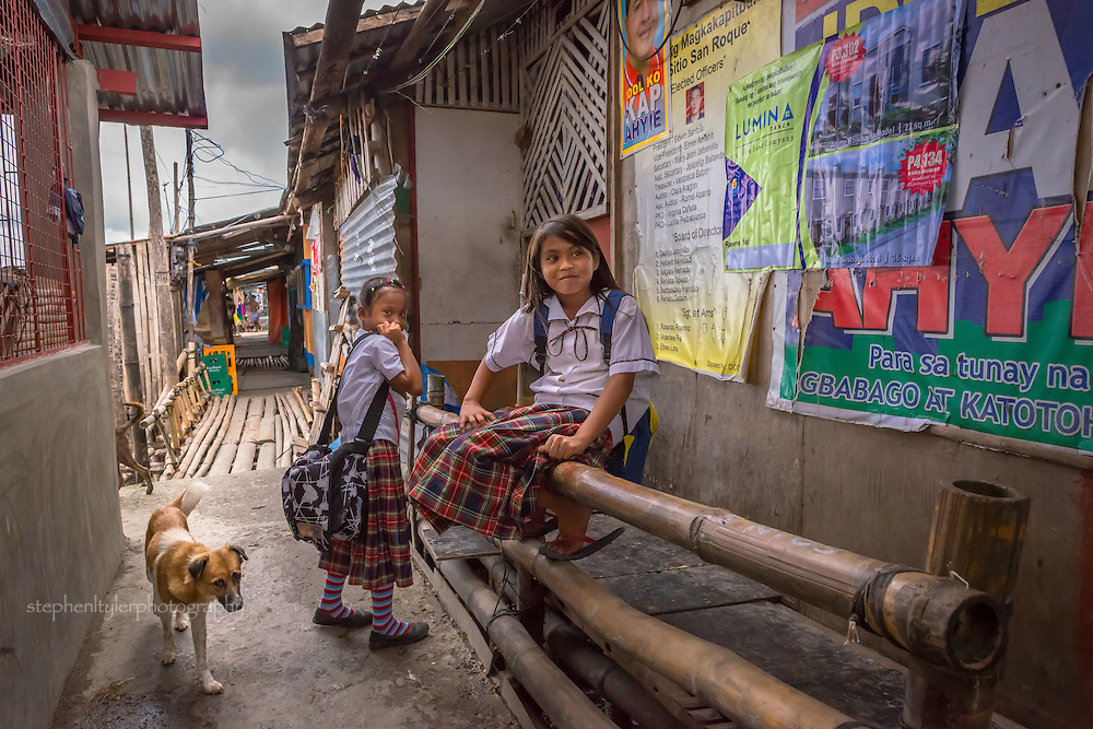 Everyday life in a fishing village community with nearly everything built from bamboo on top of stilts on the edge of a lake. Two girls in school uniform demonstrate the desire of their family to get them an education.