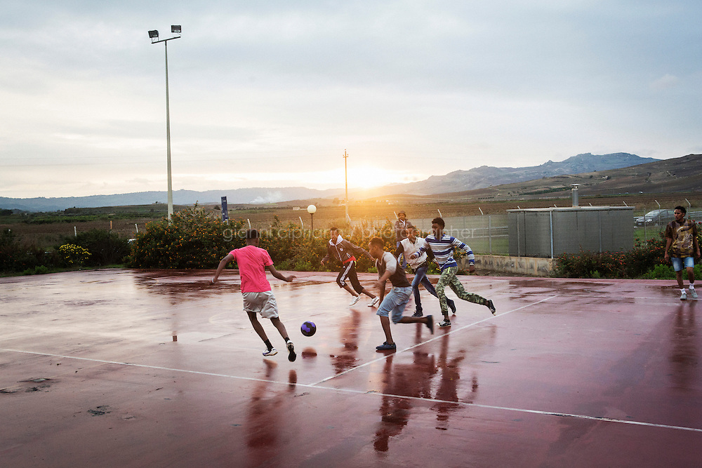 MINEO, ITALY - 26 NOVEMBER 2014: Eritrean asylum seekers play football on a basketball field of the CARA (Accommodation Centre for Asylum Seekers) in Mineo where approximately 4,000 asylum seekers live, in Mineo, Italy, on November 26th 2014.<br /> <br /> By law, asylum-seekers can be held for 35 days in a CARA. In reality, the average stay is closer to a year.The Cara is located at the &quot;Residence degli Aranci&quot; (Residence of the Oranges), a small town built to accomodate the families of US soldiers operating at the Naval Air Station of Sigonella 40km away. Since 2011 the &quot;Residence degli Aranci&quot; hosts the Accommodation Center for Asylum Seekers, which has since then hosted more than 12,000 seekers of 47 nationalities and over 200 ethnic groups. The CARA of Mineo includes 404 houses. Each housts from 7 to 11 asylum seekers.