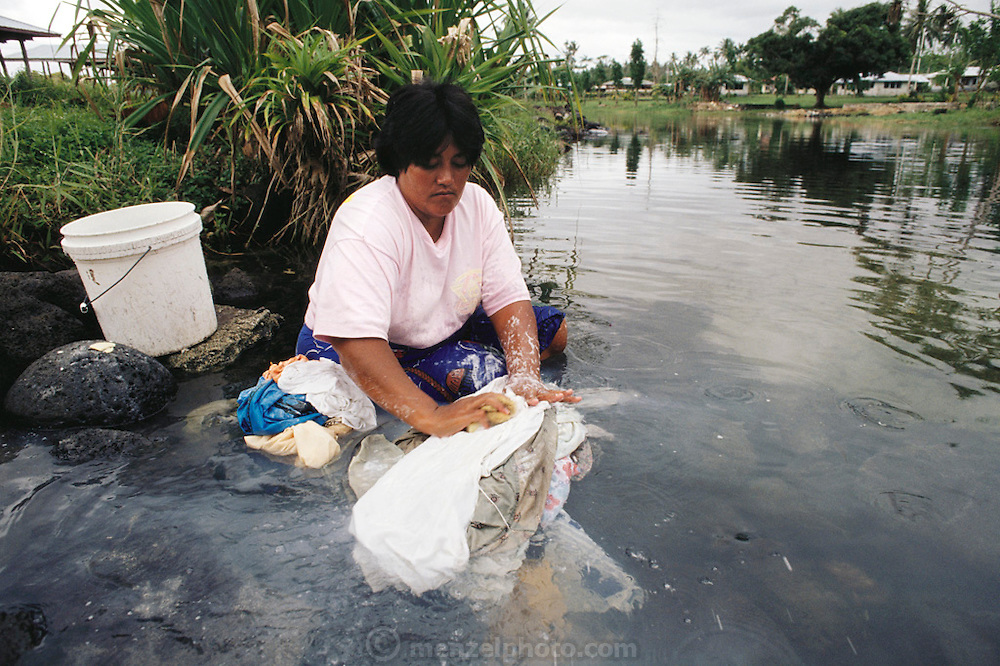 Laufafa Alatupe, 31, washes her family's clothes in a stream near the family home. Western Samoa. The Lagavale family lives in a 720-square-foot tin-roofed open-air house with a detached cookhouse in Poutasi Village, Western Samoa. Material World Project.