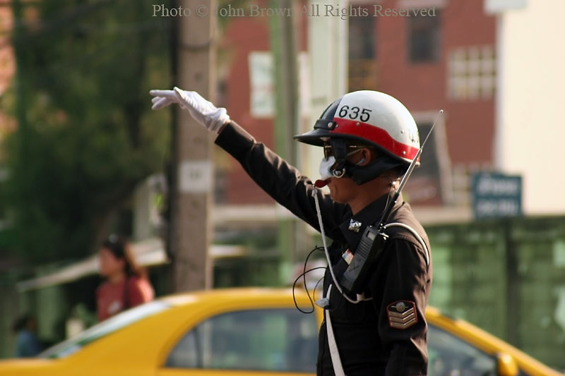 A policeman is blowing a whistle while directing traffic on a busy street in Bangkok, Thailand.
