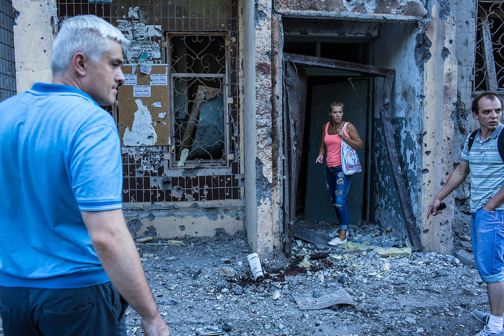 Residents survey the damage at an apartment building which was hit by a suspected grad rocket strike on Tuesday, July 29, 2014 in Donetsk, Ukraine.