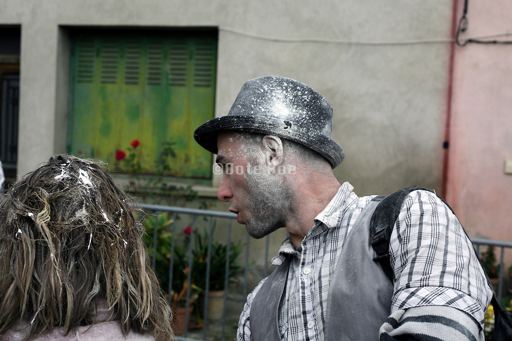 party with man having white powder on his face and hat with other person foam in her hair