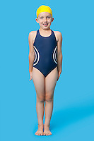Portrait of a happy young girl in swimming costumes over blue background