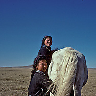 Mongolia. two girls are milking horse in Nohoorlol Tereelg