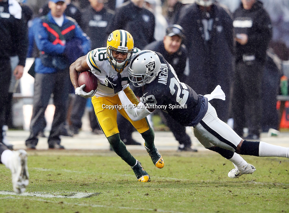 Green Bay Packers wide receiver Randall Cobb (18) gets tackled by Oakland Raiders cornerback David Amerson (29) as he catches a third down pass good for a first down in the third quarter during the 2015 week 15 regular season NFL football game against the Oakland Raiders on Sunday, Dec. 20, 2015 in Oakland, Calif. The Packers won the game 30-20. (©Paul Anthony Spinelli)