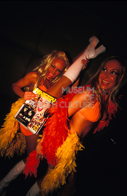 Two blonds wearing hotpants, white boots and bikini tops holding Ministry magazine and thrusting leg into the air, London, U.K, 2000s.