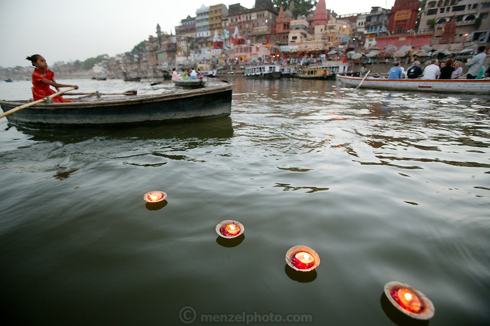 A young girl in a rowboad sells floating votive candles to mourners and tourists near the Dashashwamedh Ghat, on the Ganges River in Varanasi, India. The most visited ghat of Varanasi by religious pilgrims, Dashashwamedh ghat is the most beautiful ghat in the city. The ghat is close to the famous 'Vishwanath Temple' and is therefore of high religious importance. The most enticing part is the evening 'Puja' performed by the group of priests. Also known as the 'Fire Puja', the ceremony is a dedication to River Ganges, Sun, Lord Shiva, Fire and the whole universe. The Ghats finds mention in the old religious texts, as it is said that lord Brahma created the ghats to welcome lord Shiva.