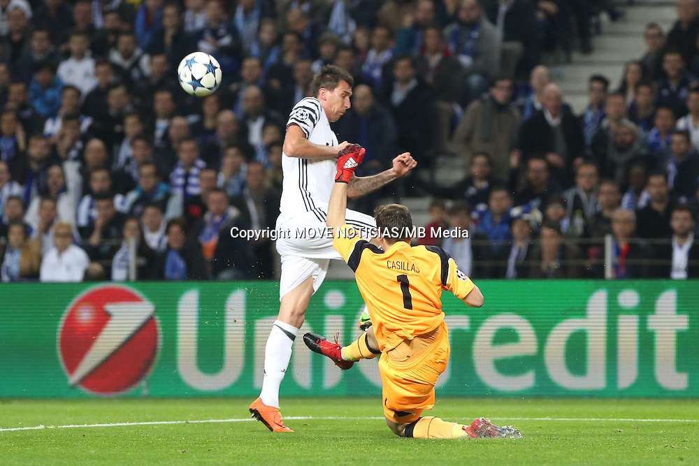 Porto goalkeeper Iker Casillas comes off his line to tackle Juventus striker Mandzukic