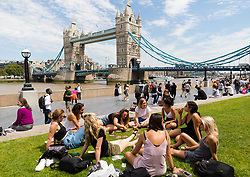 © Licensed to London News Pictures. 05/07/2019. London, UK.  A group of friends play a game of cards during warm and sunny weather near Tower Bridge in London on Friday lunchtime. The UK continues to enjoy seasonally warm weather this week, but rain is forecast across the country during the next few days. Photo credit: Vickie Flores/LNP