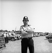 Policeman standing in car park with arms crossed, Glastonbury, Somerset, 1989