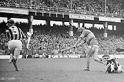 Tipperary makes a swing for the goal as Kilkenny player falls to the ground in an attempt to tackle him during the All Ireland Minor Hurling Final, Tipperary v Kilkenny in Croke Park on the 5th September 1976.