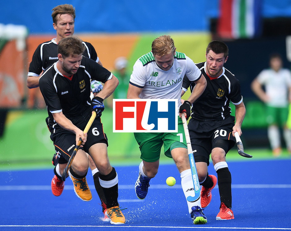 Ireland's Michael Watt (C) tries to get past Germany's Martin Haner (L) and Martin Zwicker during the men's field hockey Germany vs Ireland match of the Rio 2016 Olympics Games at the Olympic Hockey Centre in Rio de Janeiro on August, 9 2016. / AFP / MANAN VATSYAYANA        (Photo credit should read MANAN VATSYAYANA/AFP/Getty Images)