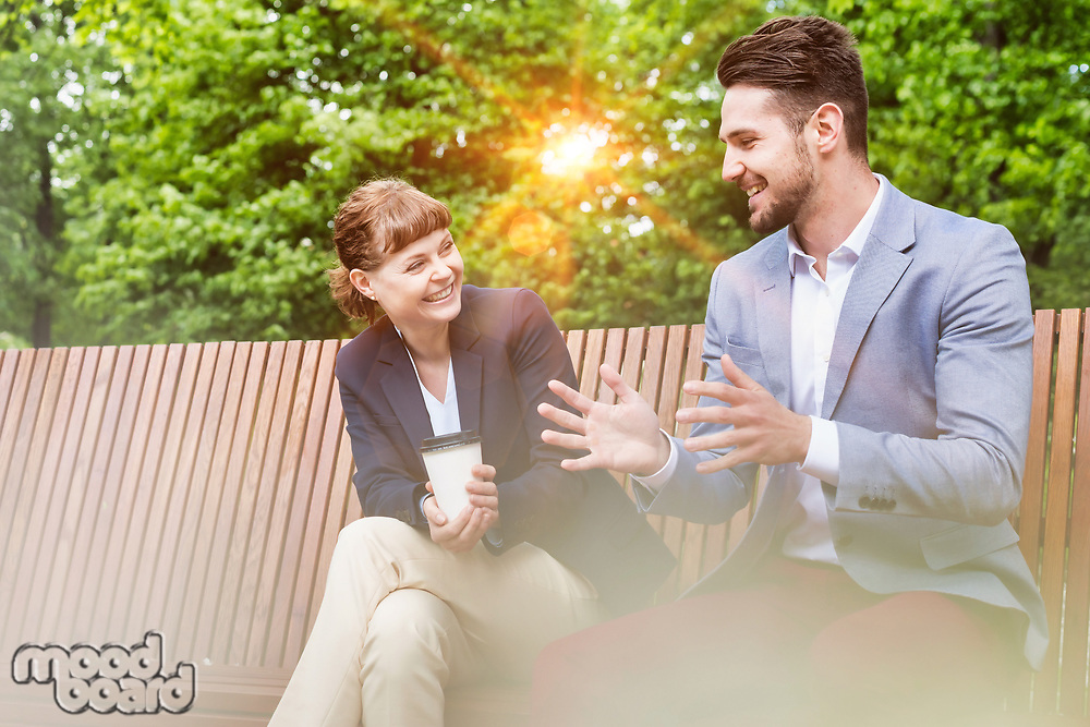 Portrait of handsome businessman gesturing and talking to businesswoman while sitting on bench during office break