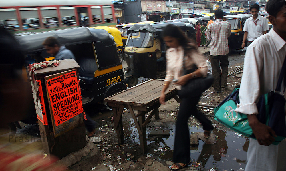 People walk past advertisements of English Speaking classes displayed on a road, in Mumbai, India, on Monday August 20, 2007. Photographer:  Prashanth Vishwanathan