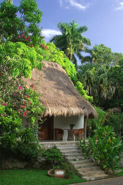 Mexico, Yucatan, Chichen Itza, thatched roof bungalow and garden at Mayaland Hotel, PR
