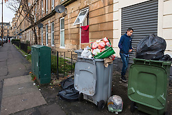 Bins full of rubbish on street in Govanhill district of Glasgow, Scotland, United Kingdom