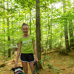 A girl walks her dog on a trail near Page Pond in Meredith, New Hampshire.