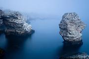 Rocky sea coast hidden by the fog