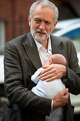 ©  London News Pictures. 19/07/2015. London, UK. JERMY CORBYN holding 4 week old Faolán Murphy O'Donnell as he arrives at the venue. Labour leadership candidates Jeremy Corbyn, Yvette Cooper, Liz Kendall and Andy Burnham attend a hustings at the Camden Centre in London. The new leader is due to be announced in September 2015.  Photo credit: Ben Cawthra/LNP