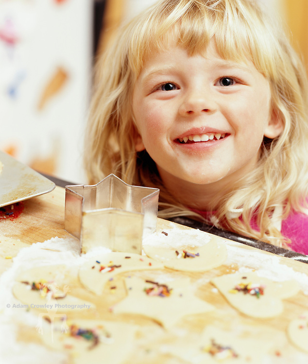 Girl (4-5) smiling with decorated cookies in foreground
