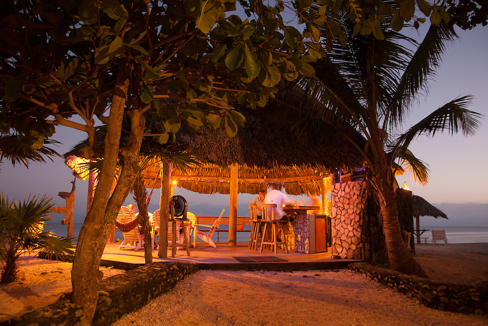 Central America, Honduras, Bay Islands, Utila, Utopia Village, people at beachside bar in thatched-roof palapa at sunset.  PR