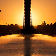 The rising sun silhouettes the Washington Monument, with the Lincoln Memorial Reflecting Pool in the foreground.