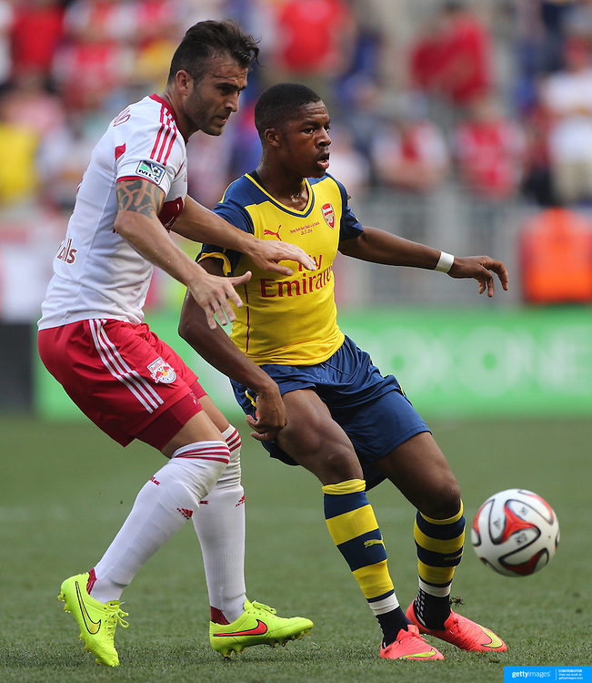 Chuba Akpom, (right),  Arsenal, challenged by Armando New York Red Bulls, during the New York Red Bulls Vs Arsenal FC,  friendly football match for the New York Cup at Red Bull Arena, Harrison, New Jersey. USA. 26h July 2014. Photo Tim Clayton