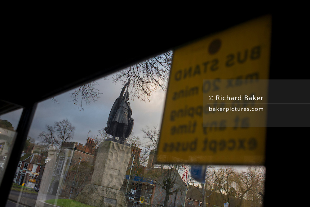 "Seen through the window of a dirty bus stop is the statue (by sculptor Hamo Thornycroft) of Saxon King Alfred that overlooks a modern Winchester, Hampshire, England. Alfred the Great (849 - 899) was King of Wessex from 871 to 899. Alfred successfully defended his kingdom against the Viking attempt at conquest, and by his death had become the dominant ruler in England. He is the only English monarch to be accorded the epithet ""the Great"". The Thornycroft statue was unveiled during the millenary celebrations of Alfred's death."