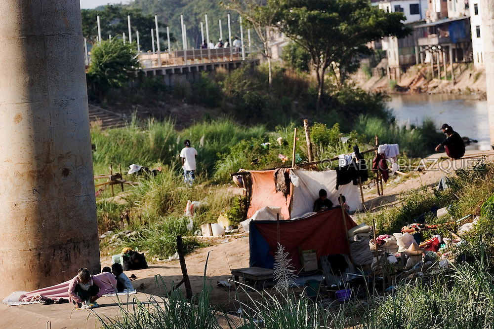 People living in the shore of the Moei River in between the Thai and Burma borders on December 19 of 2006, near Mae Sot, Thailand. Ethnic minority people sell burmese goods, and fish, crabs and plants collected from the Moei River in Thai border side.They live along the Moei river in between both borders..Burma has since 1962 been ruled by dictator Burman Regimes. Pro democrats and minority ethnics have since been object of human rights abuses and armed minority groups has appeared bringing a state of Civil War..This situation makes every days people to flee their villages to go to Thailand.